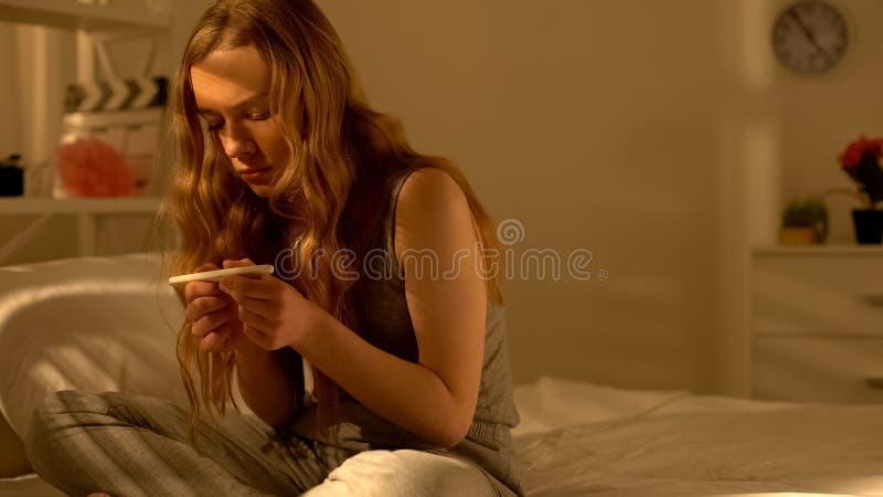 Zenuwachtige de zwangerschapstest van de tienerholding in handen, jonge leeftijdsfout, probleem stock foto