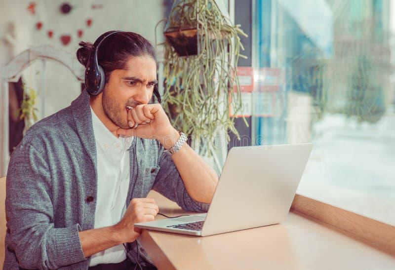 Zenuwachtige mens in hoofdtelefoons die vuist bijten die aan laptop kijken stock fotografie