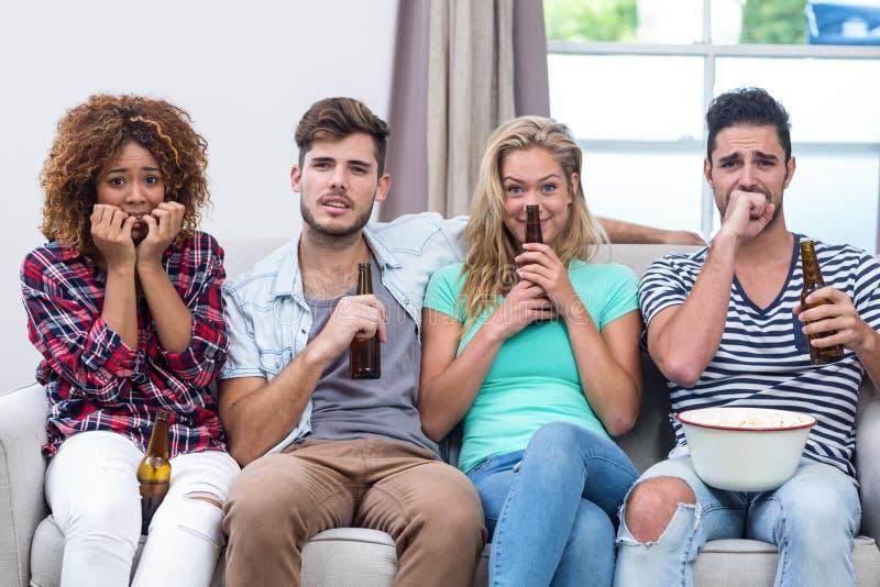 Zenuwachtige multi-etnische vrienden die op TV thuis letten royalty-vrije stock foto