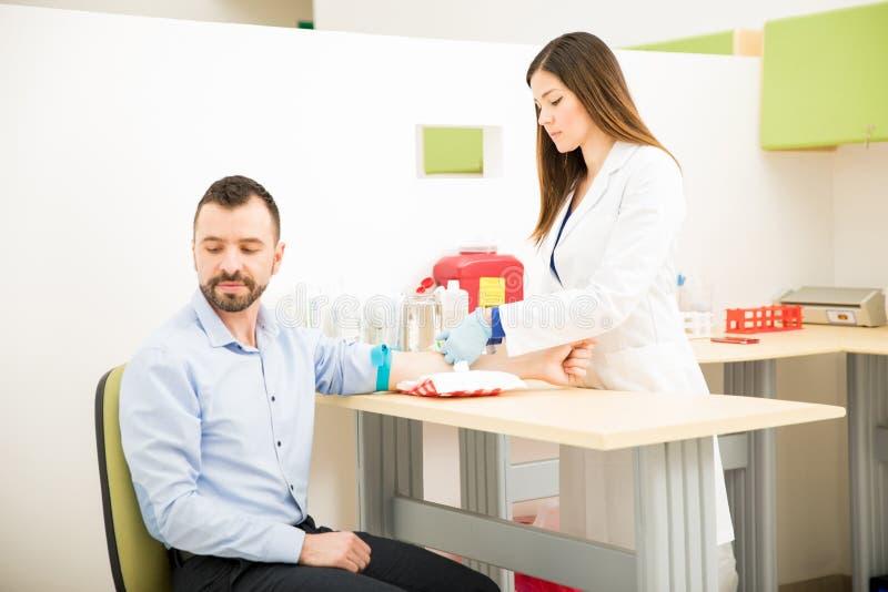 Zenuwachtige patiënt die een bloedonderzoek krijgen royalty-vrije stock fotografie