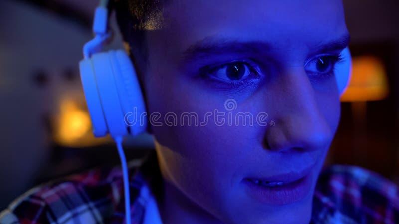 Zenuwachtige tiener die in hoofdtelefoons videospelletjes op laptop, extreem close-up spelen royalty-vrije stock afbeeldingen