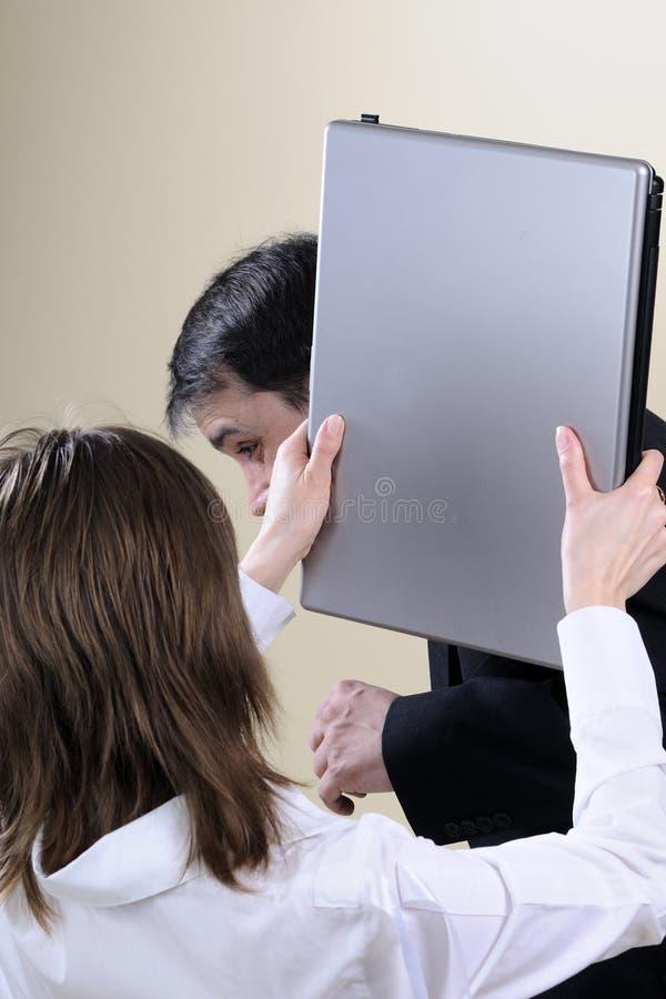 Zenuwachtige vrouw die de mens met kantoorbenodigdheden raakt stock foto
