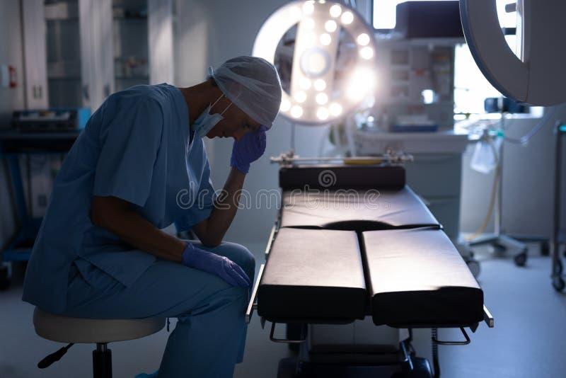 Zenuwachtige vrouwelijke chirurgenzitting in verrichtingsruimte bij het ziekenhuis stock afbeelding