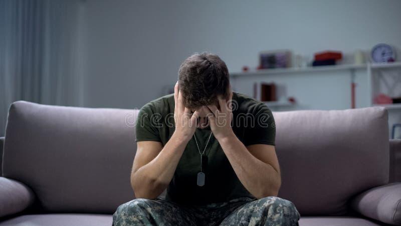 Zenuwelijk mannelijk militair lijden depressie, alleen thuis zitten, PTSD-concept stock afbeelding