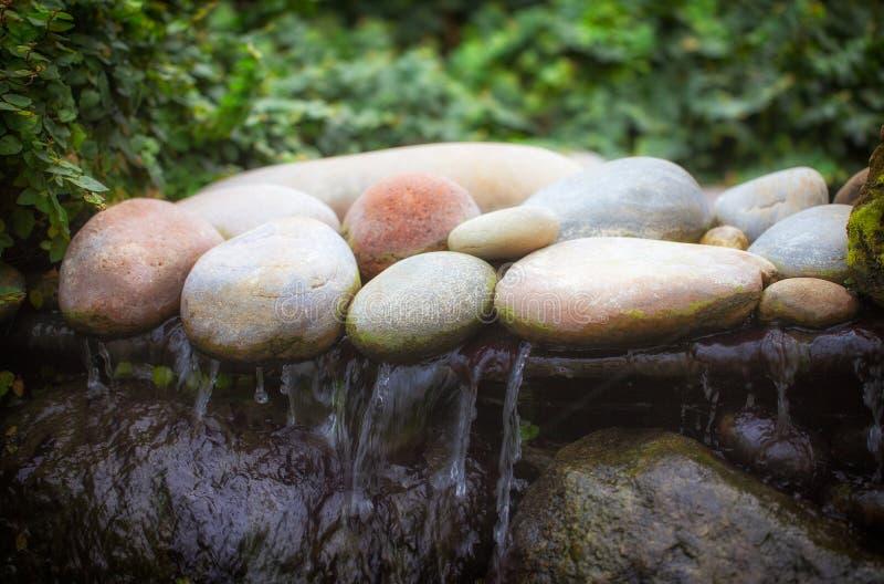 Zenwaterval Zacht beeld van stenen over het bewegen van water stock afbeeldingen