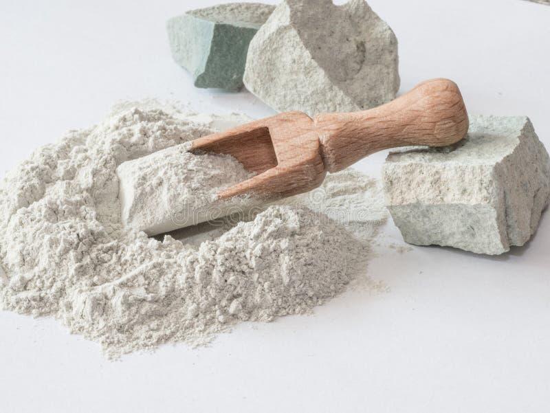 Zeoliet ruwe poeder en stenen op witte achtergrond stock foto's
