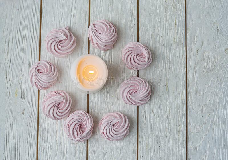 Zephyr lined in a circle shape with burning candles on a white background. Flat lay. Top view. Pink sweet homemade zephyr or. Merengue Marshmallow Zephyr lined stock images
