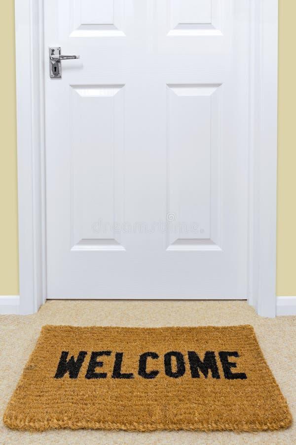 Zerbino benvenuto fuori di una porta. fotografia stock libera da diritti