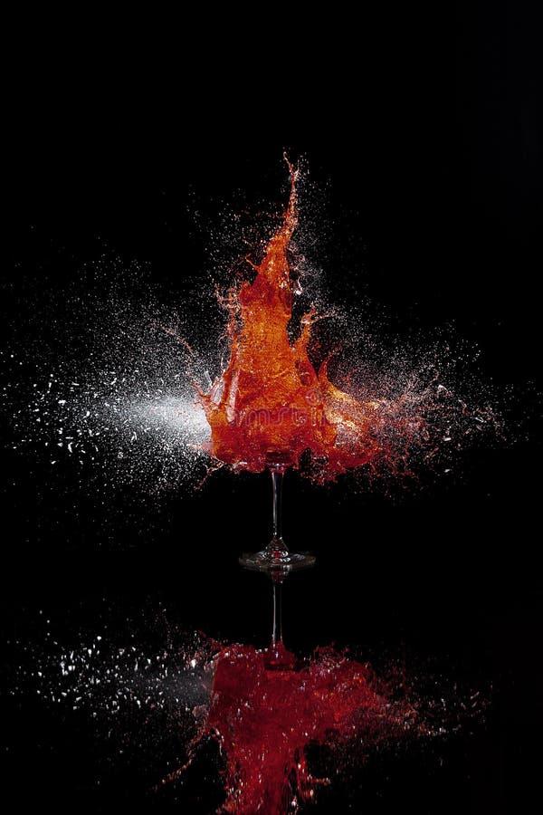 Zerbrechendes Glas mit Rotwein stockfotos