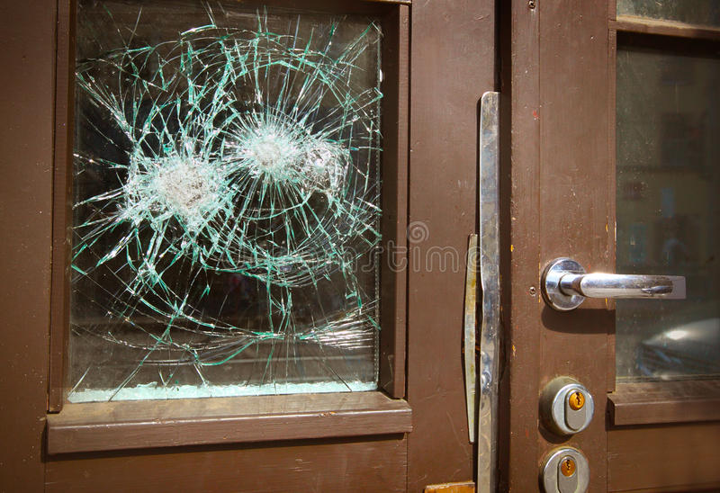 Zerbrochene Fensterscheibe auf Tür stockbild
