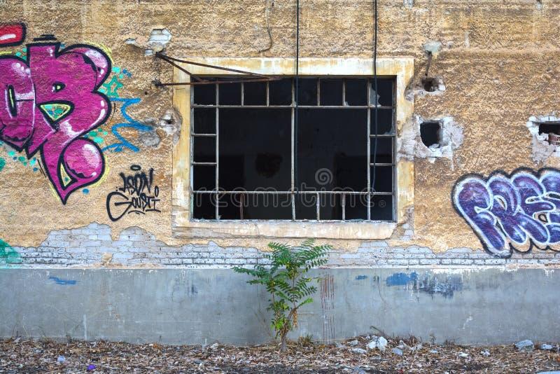 Zerbrochene Fensterscheibe in einer alten Backsteinmauer lizenzfreies stockbild