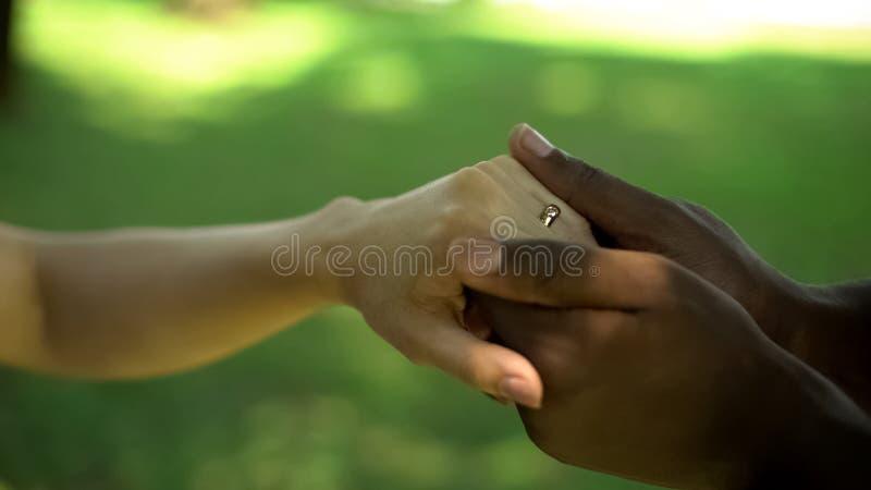 Zeremonie der interkulturellen Ehe, Mannholding-Frauenhand mit goldenem Ring auf Finger stockfotografie