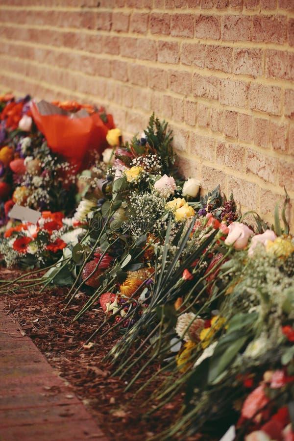 Zeremonielle Blumen, die Backsteinmauer zeichnen lizenzfreie stockfotografie