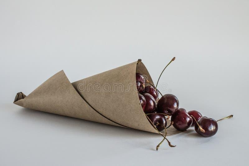 Zerfallene Beeren von reifen Kirschen in einer Papiernahaufnahme der gerollten Tasche lizenzfreies stockfoto