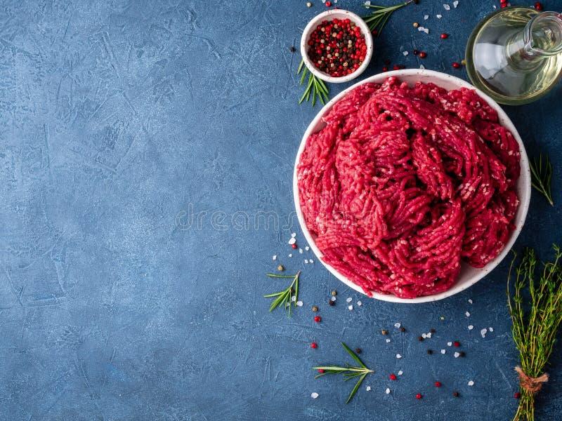 Zerkleinern Sie Rindfleisch, Hackfleisch mit Bestandteilen für das Kochen auf dunklem Blauem lizenzfreies stockfoto