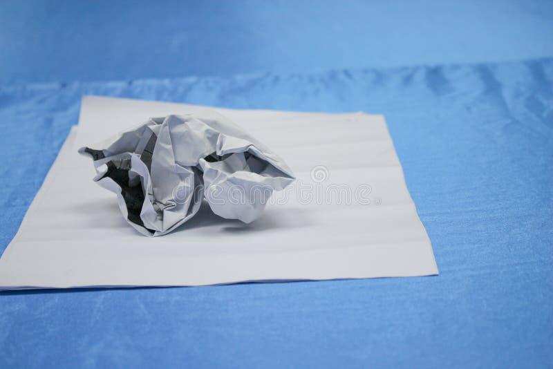 Zerknitterter Papierklumpen und Beschaffenheit auf blauem Tabellenhintergrund stockfoto