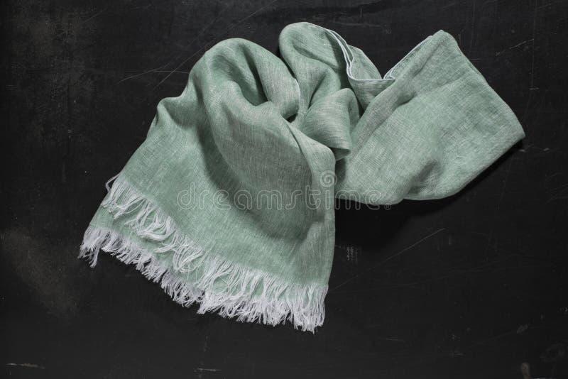 Zerknittertes einfaches grünes Handtuch auf glatter schwarzer Oberfläche stockfotografie