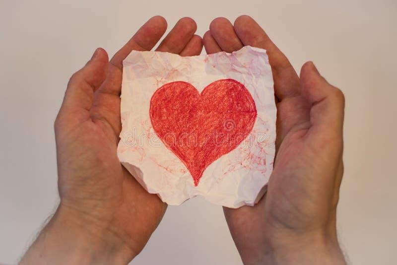 Zerknittertes Herz in seinen Händen stockfotografie