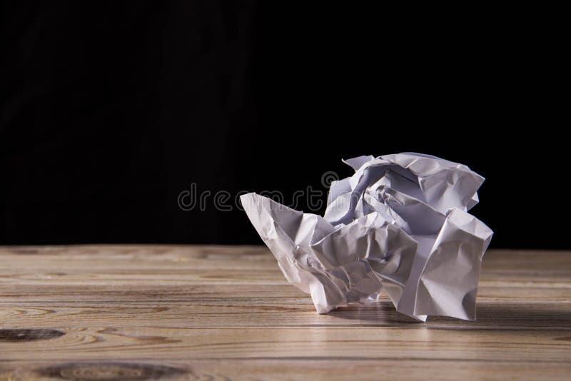 Zerknittertes Weißbuch auf einem Holztisch lizenzfreie stockfotos