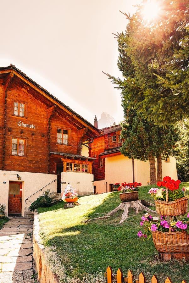 Zermatt Schweiz - 24 Augusti, 2016: Inre gård med den traditionella schweiziska chalet med blommor på den Zermatt semesterortbyn  arkivbild