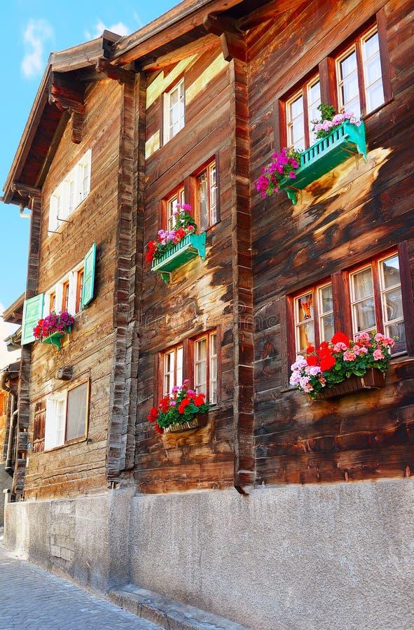 Zermatt Schweiz - Augusti 24, 2016: Traditionell schweizisk chalet med blommor på balkonger på den Zermatt byn, i Schweiz in arkivbilder