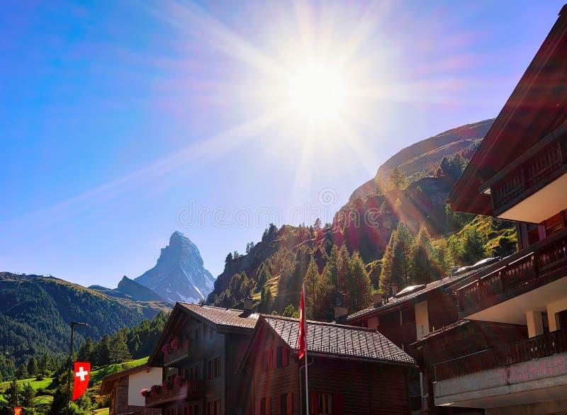 Zermatt Schweiz - Augusti 24, 2016: Traditionella schweiziska chalet i Zermatt med den Matterhorn toppmötet med flaggor, Schweiz  royaltyfri bild