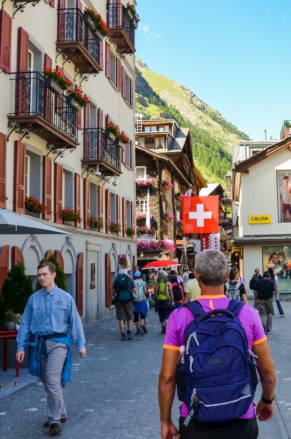 Zermatt Schweiz - Juli 10 2019: Turister som går i gatan av den alpina byn Zermatt i sommarsäsong Vandring fotvandrare schweizare royaltyfria foton
