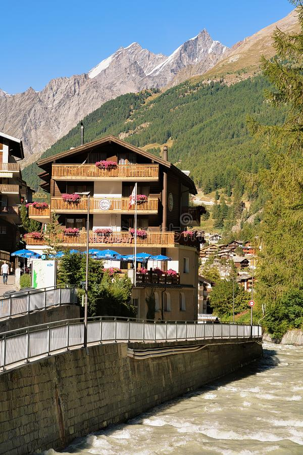 Traditional Swiss chalets and Gornera River in resort town Zermatt. Zermatt, Switzerland - August 24, 2016: Traditional Swiss chalets and Gornera River in resort royalty free stock photos