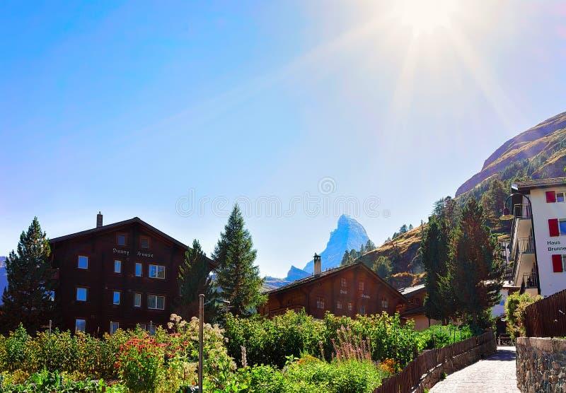 Zermatt, Switzerland - August 24, 2016: Traditional Swiss Chalets in Zermatt and Matterhorn summit, Switzerland in summer. Sunny. With ray of lights stock images