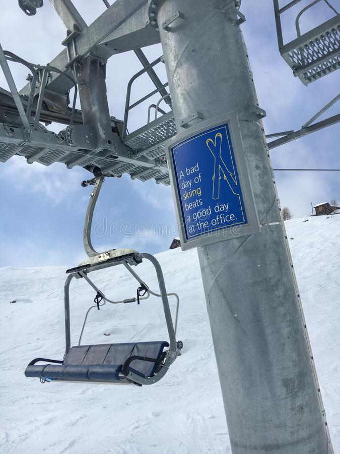 """Funny slogan an a pole of a chair lift """"A bad day of skiing be royalty free stock photos"""