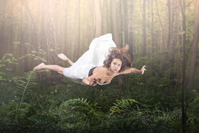 Zero gravity. Young beautiful woman flying in a dream. Forest green and glow. White dress and hair in the air. Surprise and light fright stock image