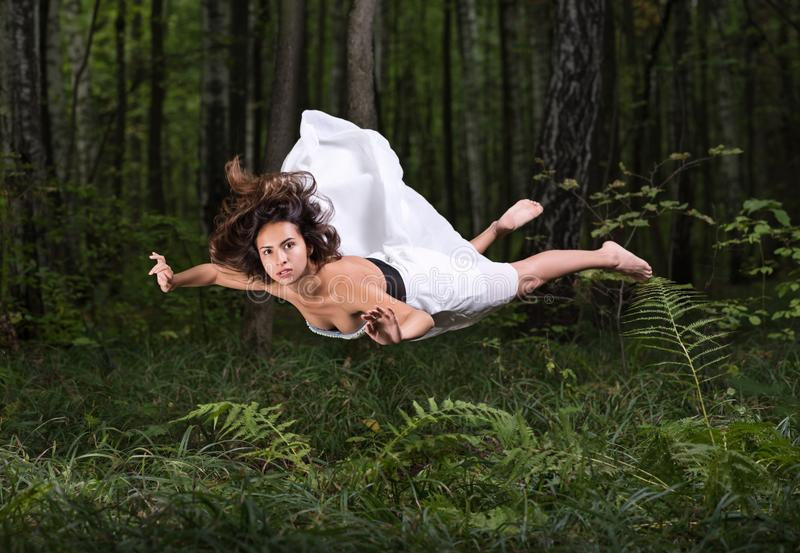 Zero gravity. Young beautiful woman flying in a dream in a summer forest. White dress and hair in the air. Surprise and light fright stock photo