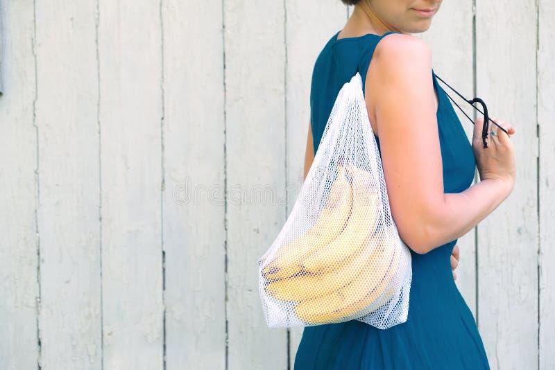 Zero ja?owy zakupy poj?cie ?adny u?ywa klingeryt Kobieta trzyma reusable przetwarzającą siatka produkt spożywczy torbę z bananami obrazy royalty free