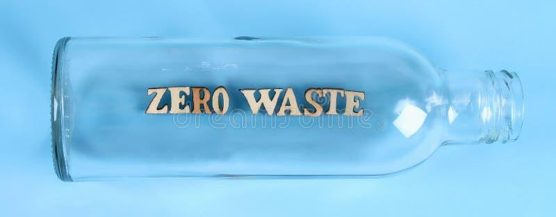 Zero waste concept. Empty glass bottle for zero waste shopping and storage on blue background royalty free stock photo