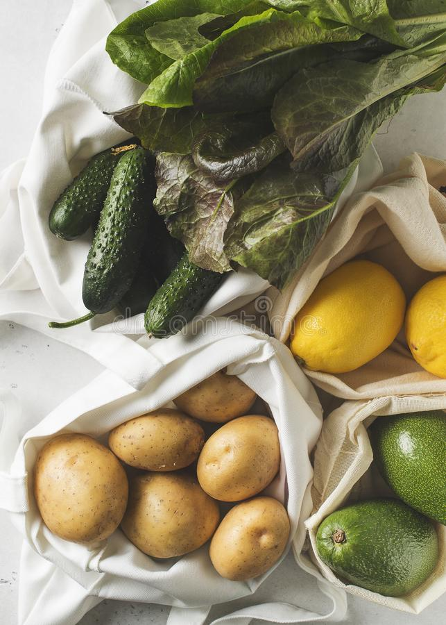Zero waste concept. Textile ecologiical shopping bags with fruits and vegetables on white background royalty free stock photos