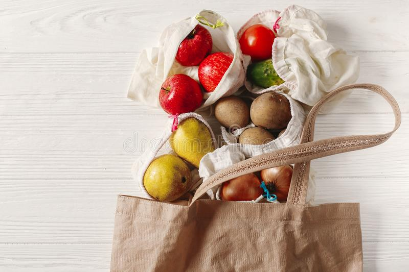 zero waste food shopping. eco natural bags with fruits and vegetables in tote, eco friendly, flat lay. sustainable lifestyle stock photo