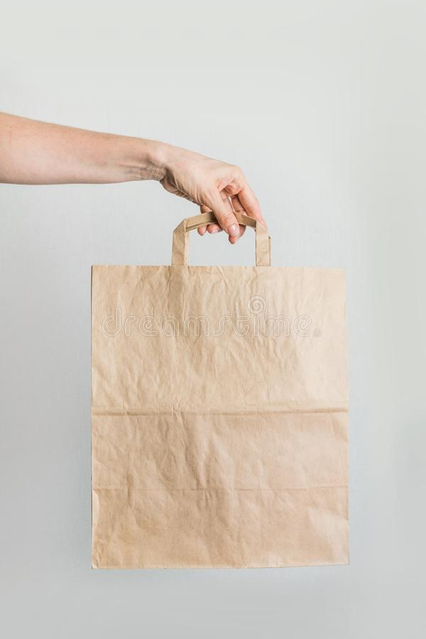 Zero waste. Paper shopping bag in women`s hand. Paper shopping bag in women`s hand. Vertical shot. Zero waste concept. Plastic free. Renewable resource royalty free stock images