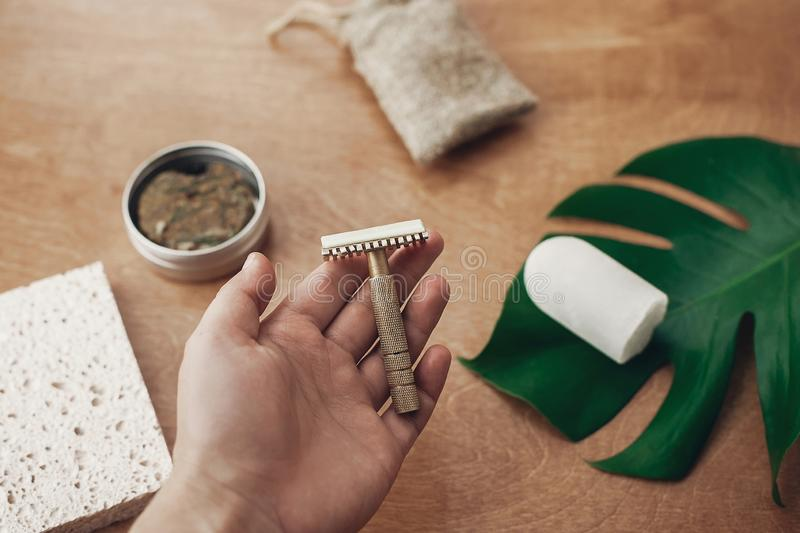 Zero waste, plastic free beauty essentials. Hand holding reusable razor for shaving on background of natural soap, solid shampoo,. Eco deodorant, on wood with stock photography