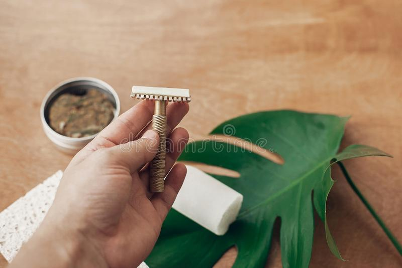 Zero waste, plastic free beauty essentials. Hand holding reusable razor for shaving on background of natural soap, solid shampoo,. Eco deodorant, on wood with royalty free stock photography