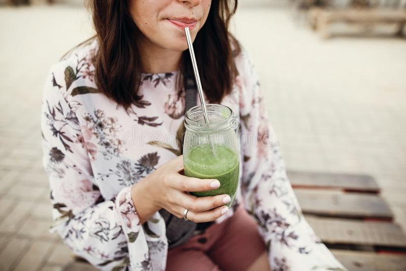 Zero waste at street food festival. Stylish hipster boho girl drinking spinach smoothie in glass jar with metal reusable straw at royalty free stock image