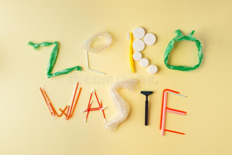 Zero waste text from plastic products on yellow background, eco-friendly earth protection concept royalty free stock image