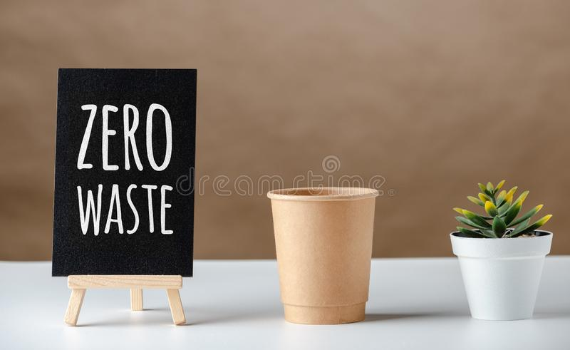 Zero waste word on blackboard with peper cup and green plant on white table and brown background.eco friendly concept.  stock photo