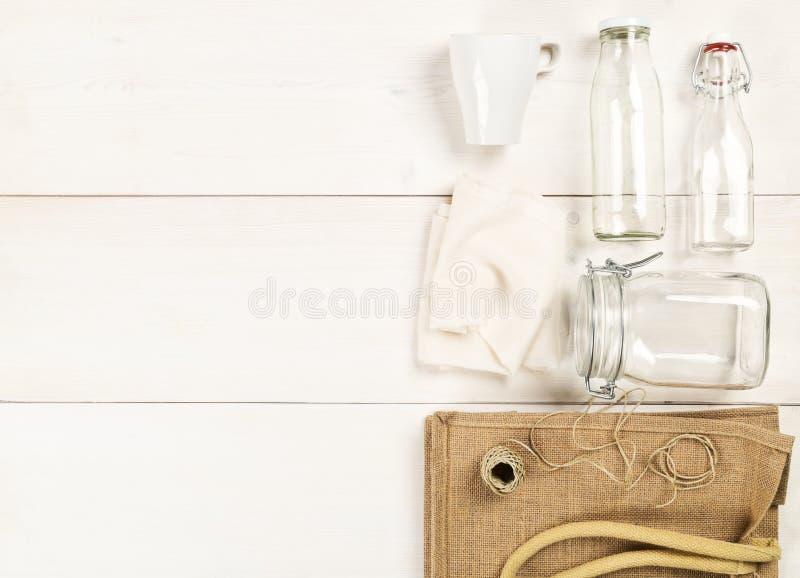 Zerowe odpady lub niemarnowane naczynia handlowe z workiem na białe drewniane podłoże stołowe, szklane butelki i bawełna fotografia royalty free
