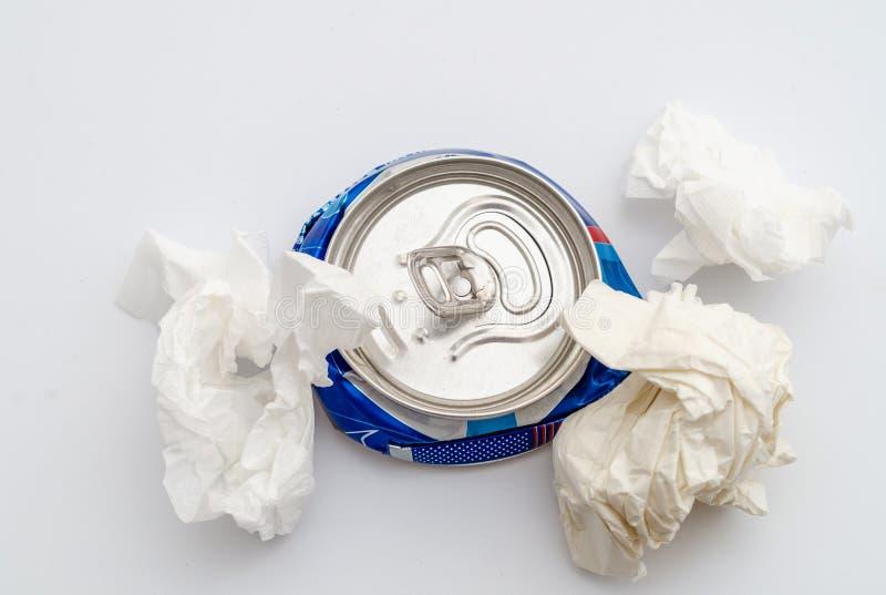 Zerquetschte komprimierte Aluminiumdose eines gekohlten Getränks mit zerknitterten Blättern Papier Verschmutzung, Abfall, Ökologi lizenzfreies stockbild