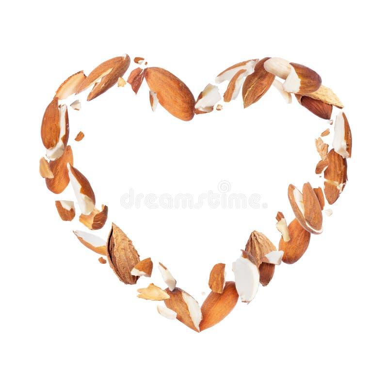 Zerquetschte Mandeln in der Luft in Form eines Herzens, lokalisiert auf einem weißen Hintergrund stockbilder