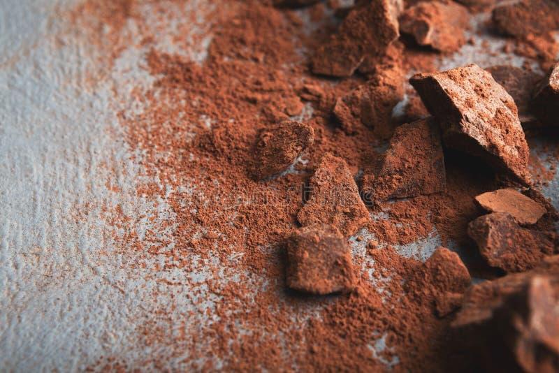 Zerquetschte Schokoladenstücke und -kakao auf grauem Hintergrund lizenzfreies stockfoto