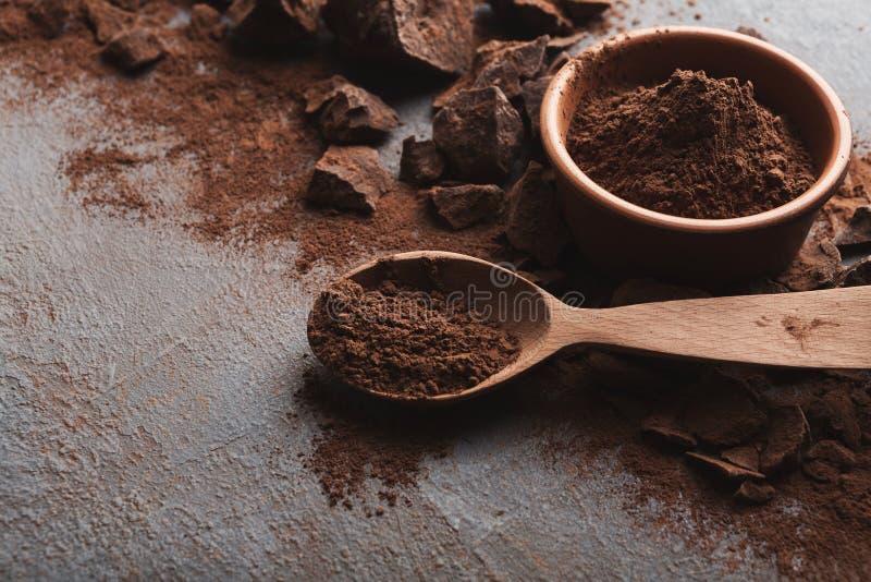Zerquetschte Schokoladenstücke und -kakao auf grauem Hintergrund stockbilder