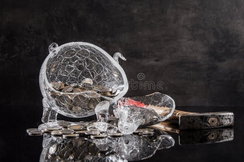 Zerquetschtes Sparschwein mit Münzen und Hammer lizenzfreie stockfotos