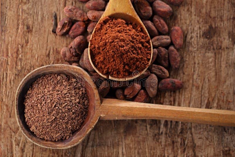 Zerriebene dunkle Schokolade im alten hölzernen Löffel auf gebratenem Kakao choco lizenzfreies stockfoto