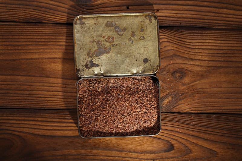 Zerriebene dunkle Schokolade im Zinn mit Kakaobohnen und festem Stück herein lizenzfreies stockbild